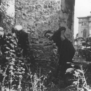 Po zakończeniu wojny, ze względu na ogrom zniszczeń, istniało realne zagrożenie, że Uniwersytet Warszawski zostanie czasowo przeniesiony do Łodzi. Jednakże studenci i pracownicy uczelni z poświęceniem pomagali w odbudowie budynków uniwersyteckich. Aż wreszcie, w grudniu 1945 r. w trudnych warunkach rozpoczęto nowy rok akademicki. Na ilustracji: Odgruzowywanie Uniwersytetu Warszawskiego, wrzesień 1945 r., zbiory Muzeum UW.