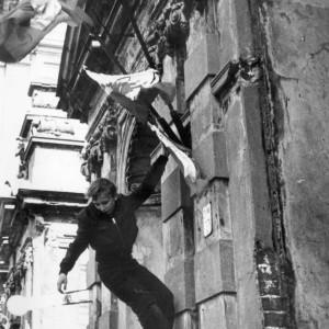 """Po wprowadzeniu stanu wojennego, 13 grudnia 1981 r. komunistyczne władze zastosowały restrykcyjne prawo, które ograniczało swobody obywatelskie. Spotkało się to ze sprzeciwem znacznej części społeczeństwa, co mocno uwidoczniło się w życiu uczelni. Na ilustracji: 1 maja 1982 r. młody manifestant zawiesza flagę na Bramie Głównej UW podczas demonstracji """"Solidarności"""", zbiory Ośrodka Karta."""