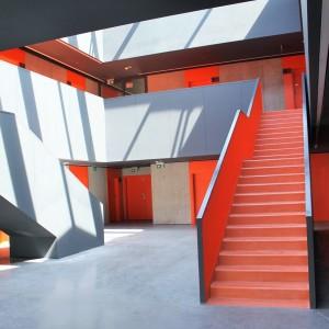 Wnętrze jednego ze studenckich bloków. Każdy z budynków ma inną kolorystykę. Dominujące kolory to: pomarańcz, żółty, zielony i szary.