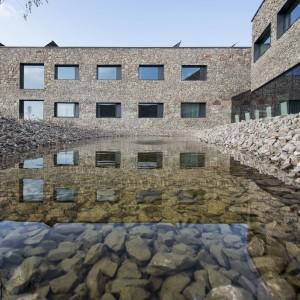 Architekci z pracowni WXCA starali się, aby gmach wkomponował się w otoczenie. Elewacja wykonana jest z miejscowego kamienia, a na dachu rosną murawy kserotermiczne, czyli takie same, jak wokół budynków.